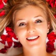 Portrait of caucasiwomlaying with rose petals in hair — Stock Photo #4620088