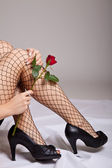 Woman legs in fishnet stockings with red rose isolated on white — Stockfoto