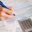 Woman hand filling income tax forms with calculator - Stok fotoraf