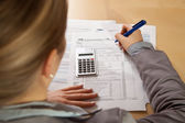 Woman hand filling income tax forms with calculator — Foto de Stock