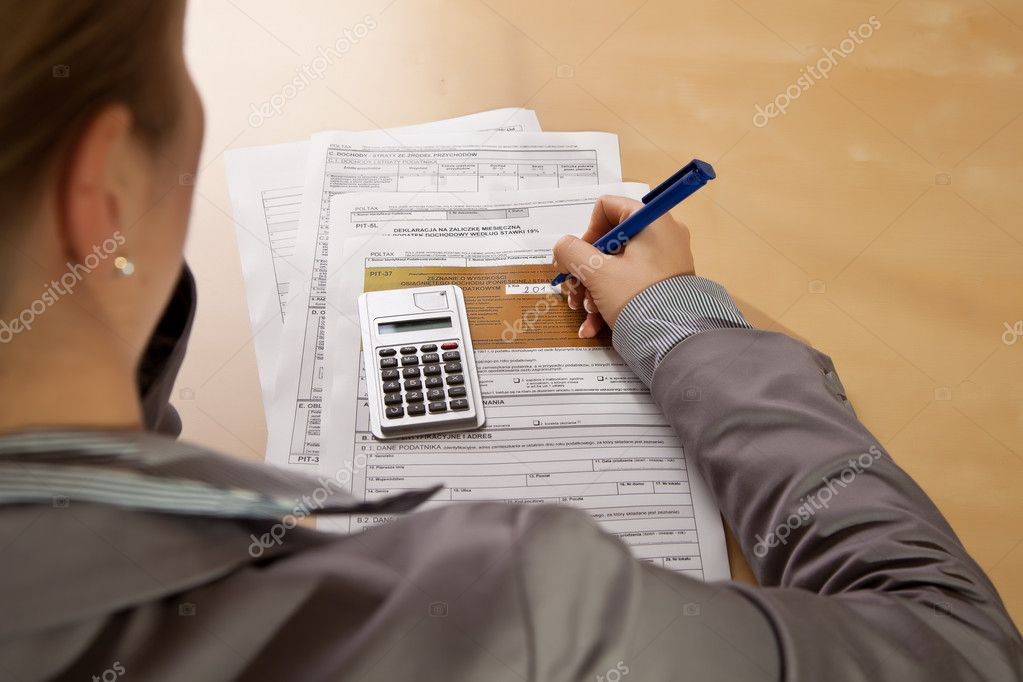 Woman hand filling income tax forms with calculator — Stock Photo #4678197