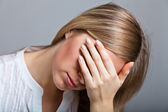 Depressed, sad woman on neutral background — Stock Photo
