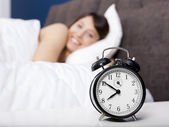 Beautiful woman on bed looking to the clock — Stock Photo