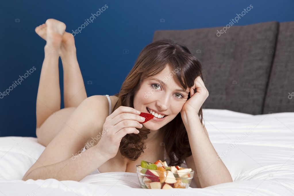 Beautiful and healthy young woman lying on bed and eating fruits — Stock Photo #5350340