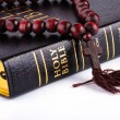 Bible with a rosary on a white background - Stock Photo