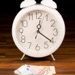 White retro alarm clock and money — Foto de Stock