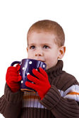 Boy drinking cup of hot tea — Stockfoto