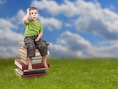 Child sitting on books — Stock Photo