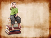 Child sitting on books — Stock Photo