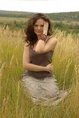 Girl sitting in an autumn field — Stock Photo