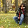 Foto Stock: Sad girl sitting under tree