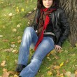 Foto Stock: Girl sitting under tree