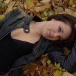 Foto Stock: Girl lying on leaves
