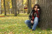Sad girl sitting under the tree — 图库照片