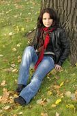 Girl sitting under the tree — Stockfoto