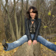 Foto Stock: Girl sitting on stump