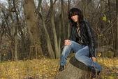 Brunette sitting on a tree stump — Stock Photo