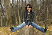 Girl sitting on a stump — Stok fotoğraf