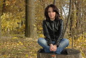 Girl sitting on a stump — Foto de Stock