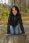Girl sitting on a stump — Stockfoto