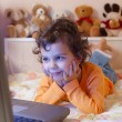 Little girl in front of a laptop - Stock Photo