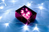 Gift box and garland lights — Stock Photo