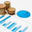 Coins and blue chart - Stock Photo