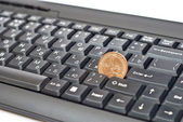 Coin on keyboard — Stock Photo