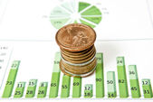 Coins and green chart — Stock Photo