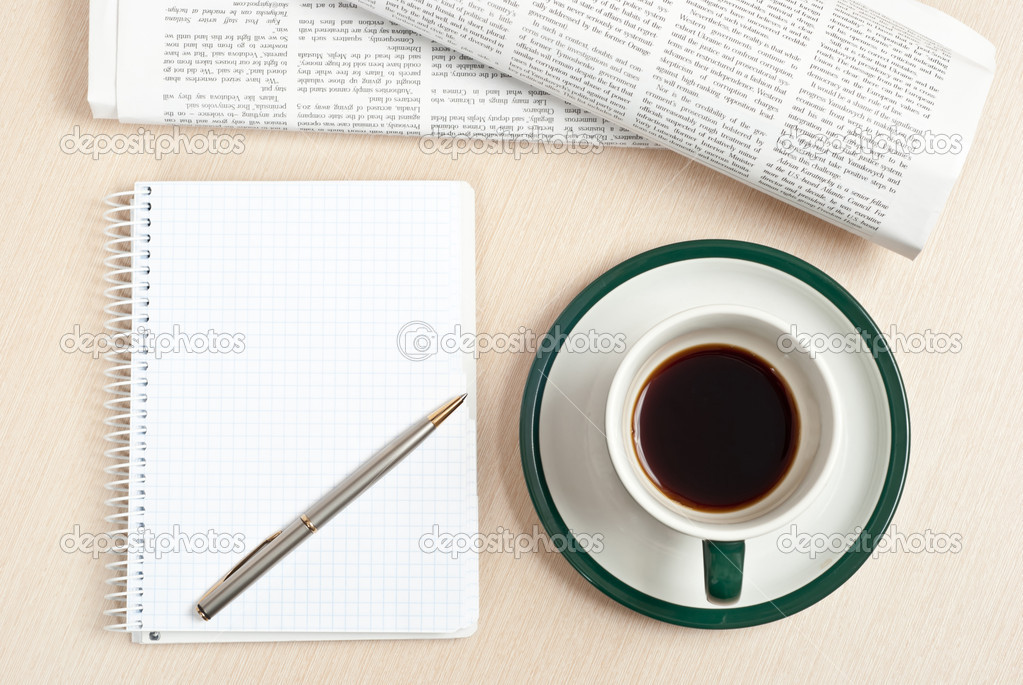 Cup of black coffee, notepad, pen and newspaper on desk  Stock Photo #5158796