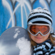 Nice girl with snowboard, graffiti background. — Stock Photo #4074684