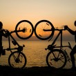 Couple with bikes watching sunset. — Stock Photo