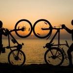 Couple with bikes watching sunset. — Stock Photo