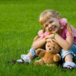 Cute little girl in grass with teddy bear. — Stock Photo