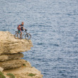 Biker on the top near the sea. — Stock Photo