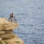 Biker on the top near the sea. — Stock Photo