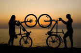 Couple with bikes watching sunset. — Photo