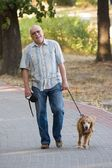 Smiling old senior with his dog. — Stock Photo