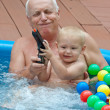 Royalty-Free Stock Photo: Grandfather and grandson having fun in the pool.