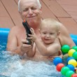 Grandfather and grandson having fun in the pool. — Stock Photo
