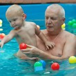 Stock Photo: Grandfather and grandson having fun in the pool.