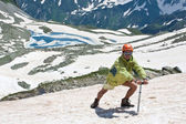 Hiker with ice-axe on snow. — Stock Photo