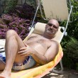 Stock Photo: Man Sunbathing In The Garden