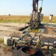 Stock Photo: Oil wells with polluted ground