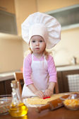 Little girl cuts dough for cookies on kitchen with form — Stock Photo