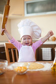 Little girl makes dough on kitchen with rolling pin — Stock Photo