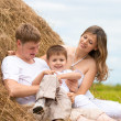 Happy family has fun in haystack together — Stock Photo #5312369