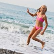 Close-up girl running from sea wave - Stock Photo