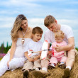 Happy family launching toy aircraft model sitting on haystack to — Stock Photo #5312457