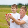 Father and son fly a kite together in summer field — Stock Photo